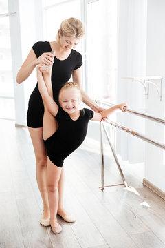Ballerina and her teacher stretching legs in ballet studio