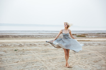 Smiling woman standing and whirling on the beach