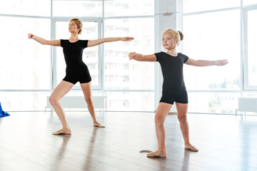 Little girl ballerina dancing with teacher in dance studio