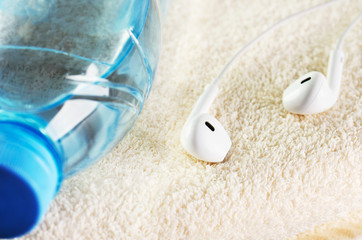 white headphones and a bottle of water close-up on a terry towel