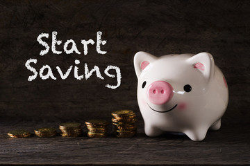 """Start saving"" words with Piggy bank and stack of golden money increased with wooden background - saving, finance and business concept"