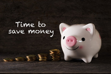 """Time to save money"" words with Piggy bank and stack of golden money increased with wooden background - saving, finance and business concept"