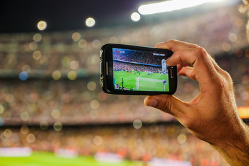 Supporter football team recording goal with mobile phone camera.