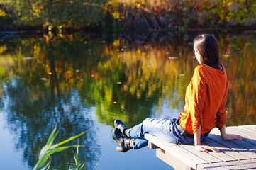 Beautiful young woman sitting on the edge of wooden jetty by the lake with autumn reflections