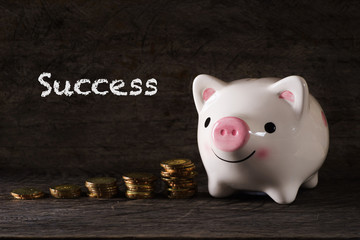 """Success"" words with Piggy bank and stack of golden money increased with wooden background - saving, finance and business concept"