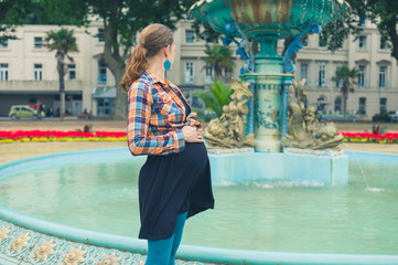 Pregnant woman by fountain in park
