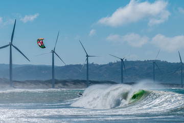 Amazing kite surfing at Philippines. Processional instructor surfing in ocean waives near windmills