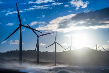Wind turbine power generators silhouettes at evening ocean coastline. Alternative renewable energy production in Philippines