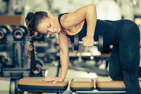 Gym Exercising. Female athlete working out with weights