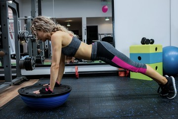 Woman doing push-up on bosu ball