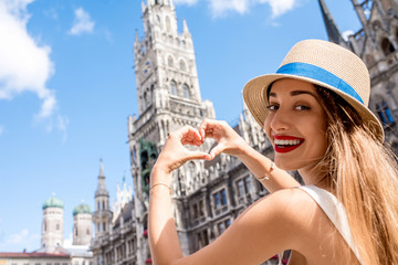 Young female tourist making heart shape with hands on the town hall building background in Munich. Having a great vacation in Germany