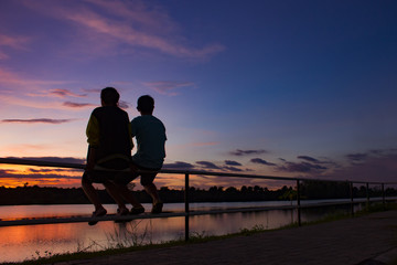 silhouette man and woman couple sitting on the iron bar at sunset