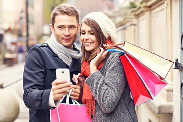Couple shopping in the city with smartphone