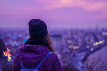 Girl looking at winter evening cityscape, purple violet sky and