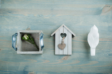 Wooden bird house, rose on blue