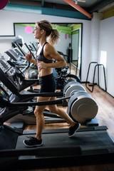 Beautiful woman exercising on treadmill