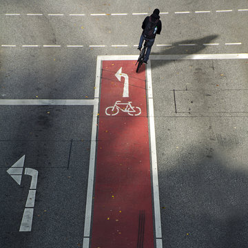 Cyclist from behind on a bike lane with symbol and arrow driving in th wrong direction