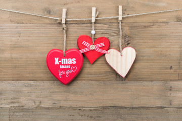 Christmas message concept: Three different wooden hearts hanging on clothesline. Wooden wall as background.