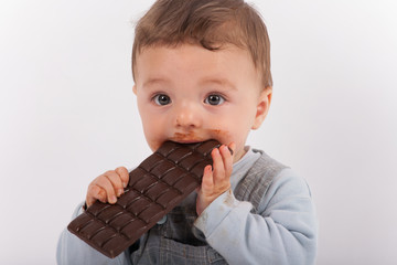 Cute toddler eating chocolate