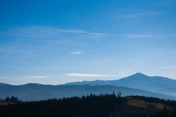 Morning fog on the mountain slopes. Carpathian Mountains. Ukraine, Europe. Color toning. Low contrast