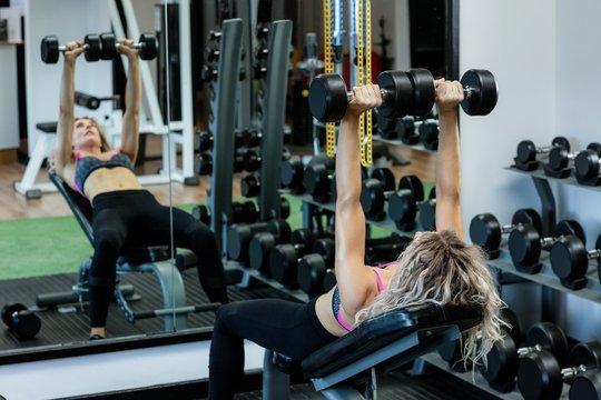 Beautiful woman lifting dumbbells