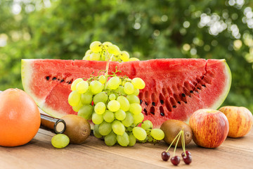 Juicy ripe red watermelon, surrounded by fruits