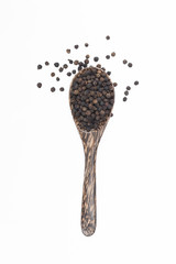 Black pepper in spoon wooden bowl isolated on white background