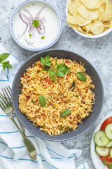 Tomato Rice served with Raita, Chips and Salad