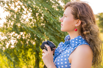 Side profile view of young woman photographer holding camera in green park with tree