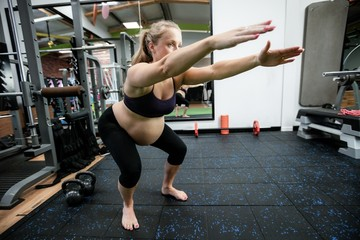 Pregnant woman performing stretching exercise