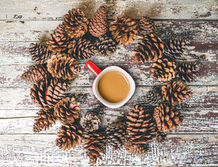 Cup of coffee and pine cones on rustic wooden background