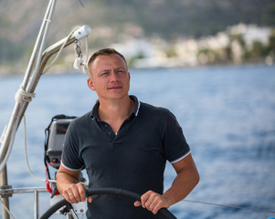 Young man at the helm of a sailing yacht.