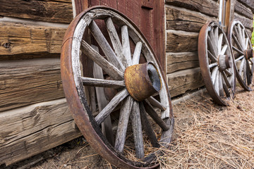 Old wagon wheels against a wall.