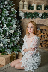 young girl sits amid the Christmas interior