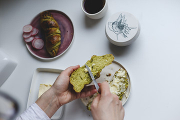 Girl preparing a breakfast sandwich with matcha rolls