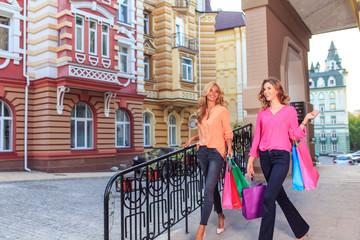 girls walking after shopping, holding shopping bags