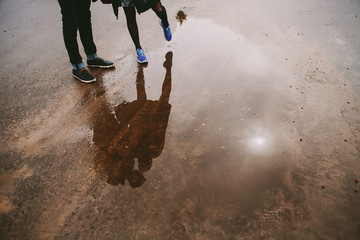 Young couple and their reflection in a puddle