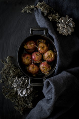 Roast apples in cocotte on slate background with kitchen towel a