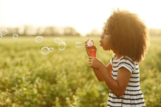 Little African American girl blowing bubbles in field