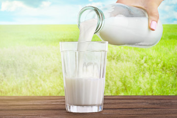 Female hand pouring milk into glass against blurred nature background. Dairy concept.