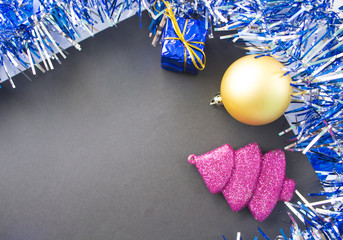 Christmas pink fir tree toy, gold ball and blue gift. Black paper with blank page.