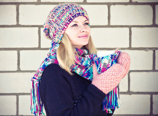 Young Woman happy smiling Face with coffee cup Winter time wearing knitted sweater hat and scarf with mittens Lifestyle concept with white brick wall on background