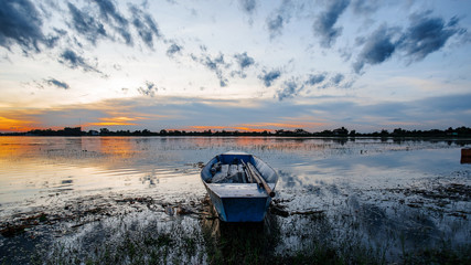 Small fishing boats beached on the riverbank in the park at sunset. Shows a silhouette of a beautiful sky reflected from the water surface.
