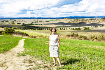 Woman standing in front of beautiful countryside in Tuscany