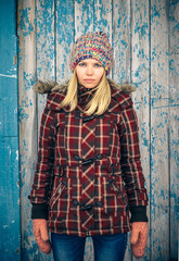 Sad Woman wearing knitted hat and mittens trendy scandinavian Lifestyle melancholy and solitude concept winter time with old wooden background