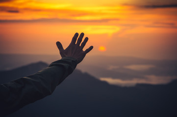 Touch the Sky concept Man Hand and Sunset mountains on background Travel Lifestyle Expression