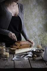 Woman cutting muesli cake on a rustic wooden table
