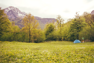 Tent Camping with man traveler outdoor beautiful mountains and green valley on background film effect colors
