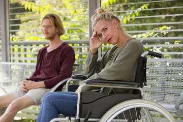 woman in wheelchair and young man sitting on bench
