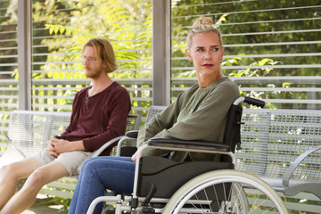 woman in wheelchair next to young man on bench